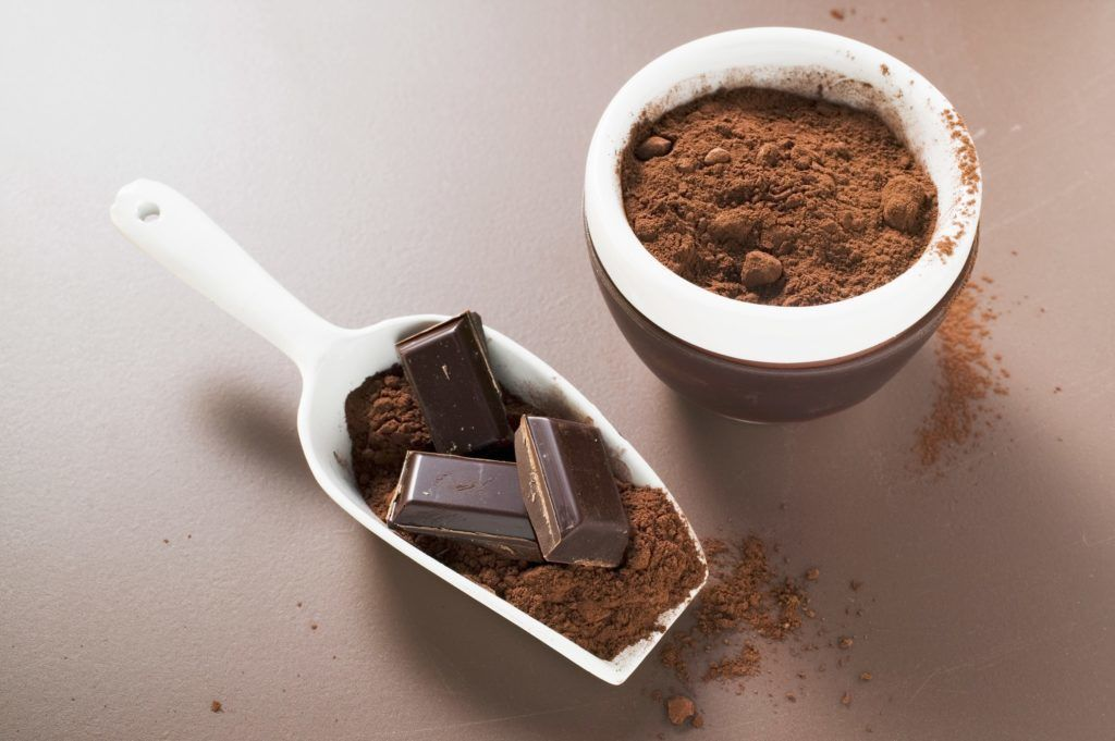 Pieces of chocolate and cocoa powder in scoop and bowl