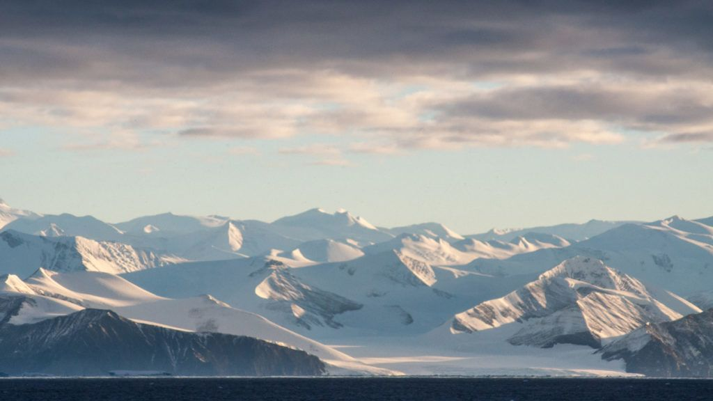 The frozen and forbidding mountains to the west of Cape Adare are the explorer's first view of Antarctica as he enters the Ross Sea