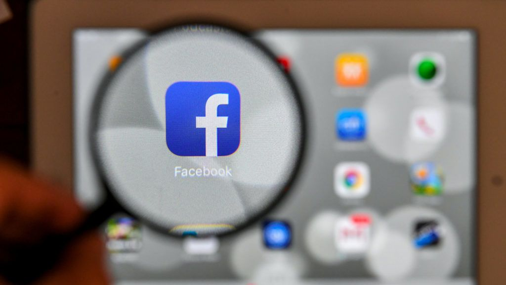 A tablet screen displays the logo of the social networking site Facebook through a magnifying glass, in Bogota, on March 22, 2018. A public apology by Facebook chief Mark Zuckerberg on March 22 failed to quell outrage over the hijacking of personal data from millions of people, as critics demanded the social media giant go much further to protect privacy. / AFP PHOTO / Luis ACOSTA