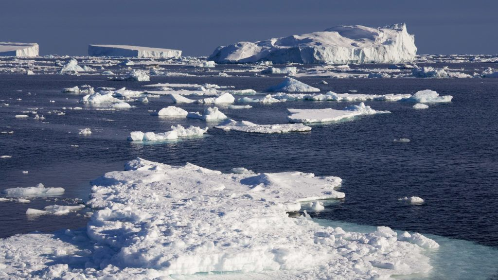 Icebergs and sea ice floating off the coast of the Antarctic Peninsula in the Weddell Sea in Antarctica.